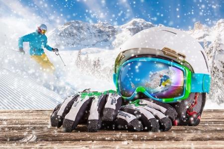 カラフルなスキー眼鏡、手袋、木製のテーブルにヘルメット。冬のスキーのテーマ。