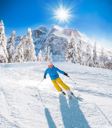 Skier skiing downhill during sunny day in high mountains Фото со стока - 94041529