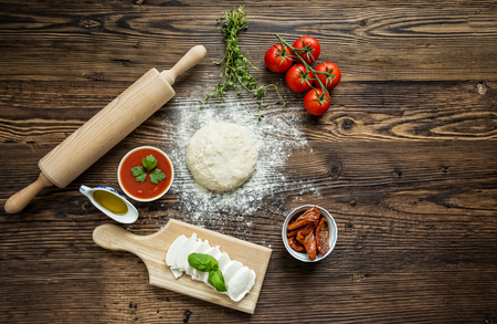 Italiaanse pizza voorbereiding, omringd door ingrediënten, bovenaanzicht. Stockfoto