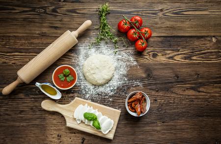Italienische Pizza Vorbereitung, umgeben von Zutaten, Ansicht von oben.