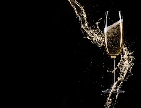Glazen champagne met splash, geïsoleerd op zwart