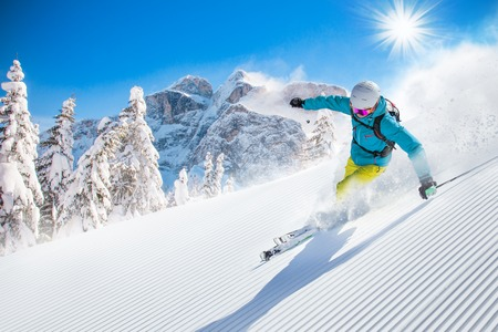 dangerous: Skier skiing downhill during sunny day in high mountains