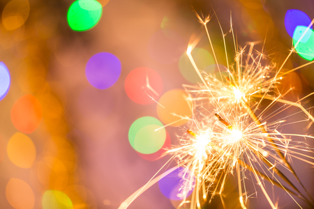 Colorful sparkler on bokeh background. Celebration or Christmas theme.