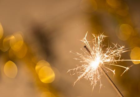 Colorful sparkler on bokeh background. Celebration or Christmas theme.