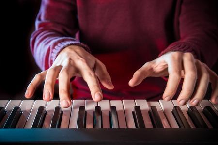 piano closeup: Mans hand playing piano. Close-up.