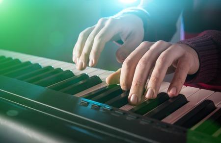 tocando piano: La mano del hombre tocando el piano. De cerca.