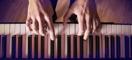 piano: La mano del hombre tocando el piano. De cerca.