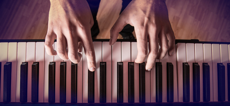 piano player: Mans hand playing piano. Close-up.