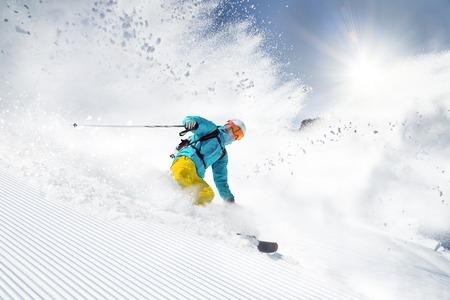 acion: Esquiador del esquí alpino durante el día soleado en alta montaña Foto de archivo