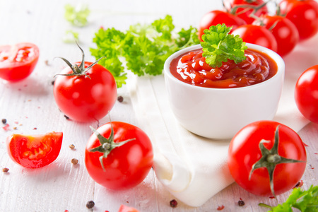 gaspacho: Bowl of tomato sauce and cherry tomatoes on wooden table, close-up. Stock Photo