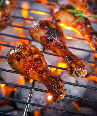 flame background: Grilled chicken Legs on the garden grill. Barbeque.