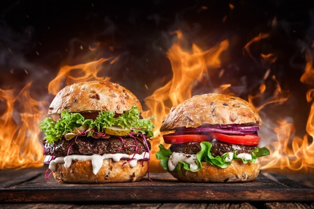 Close-up of home made burgers with fire flames.