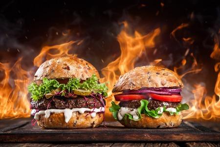 Primer plano de hamburguesas caseras con llamas de fuego.