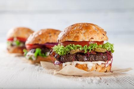 lechuga: Primer plano de la casa hizo hamburguesas en fondo de madera