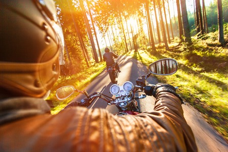 motor sport: Man seat on the motorcycle on the forest road during sunrise.