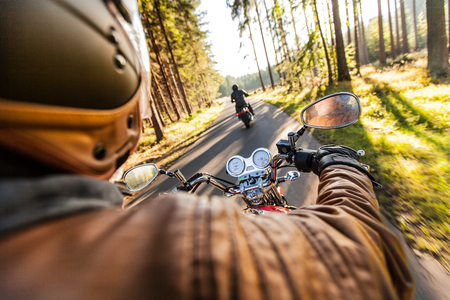 Man zitting in de motorfiets op de bosweg tijdens zonsopgang.