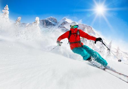 높은 산에서 화창한 날 동안 내리막 스키 스키어 스톡 콘텐츠