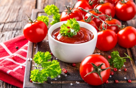 hot sauce: Bowl of tomato sauce and cherry tomatoes on wooden table, close-up. Stock Photo