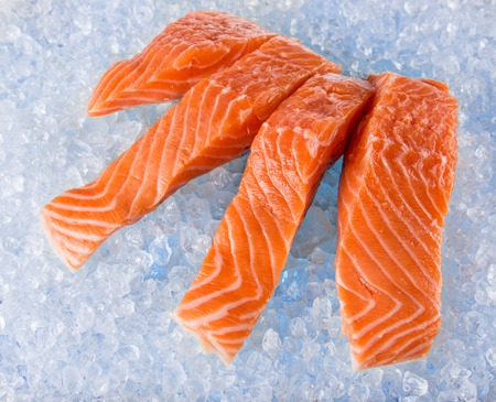 salmons: Fresh Salmon Fillets on crushed ice, close-up. Stock Photo