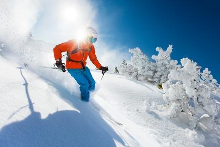 uomo rosso: Sciatore sci alpino durante giornata di sole in alta montagna Archivio Fotografico