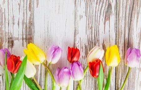 ramo de flores: tulipanes de colores en la mesa de madera. Vista superior.