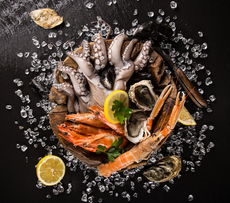 Frische Meeresfrüchte auf schwarzem Stein, close-up.