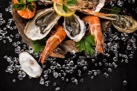 ice crushed: Fresh seafood on black stone, close-up.