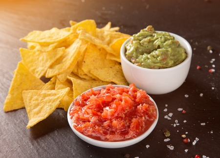 nachos: Mexican nacho chips and salsa dip on black stone background