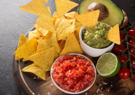 nachos mexicanos e inmersión de la salsa en el fondo de piedra negro
