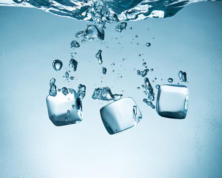 fluids: Ice cubes splashing into water, close-up