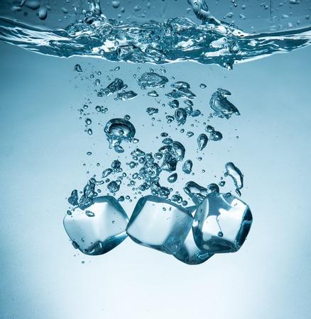 cubetti di ghiaccio che spruzzano in acqua, primo piano
