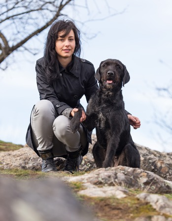 mutt: Beautiful girl with mutt black dog Amy on mountains, close-up. Stock Photo