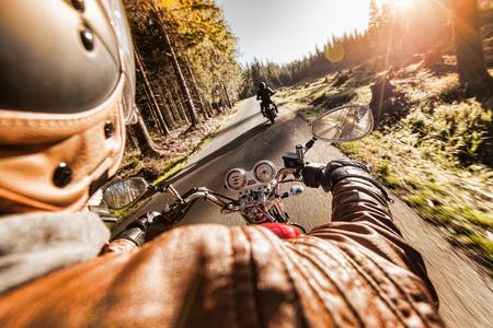 Man siège sur la moto sur la route de la forêt pendant le lever.