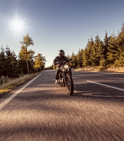 biker man: Man seat on the motorcycle on the forest road during sunrise.