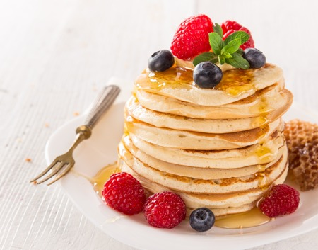maple syrup: Stack of pancakes with fresh berries, close-up.