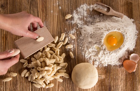 kulinarne: Homemade pasta rigate with egg, flour on a wood table, close-up.