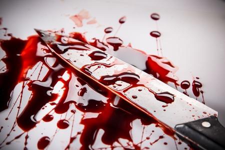 Concepto del asesinato - cuchillo con sangre sobre fondo blanco, primer plano. Foto de archivo