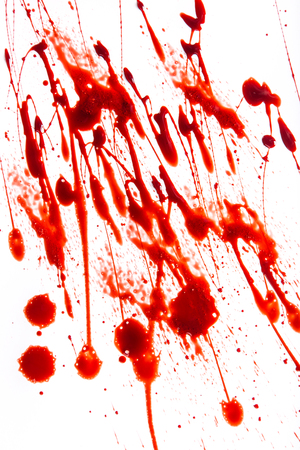a stain: Splattered blood stains on white background, close-up. Stock Photo