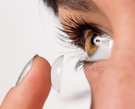 lentes de contacto: Mujer joven que pone la lente de contacto en su ojo. El tiro macro.