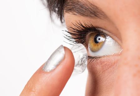 Mujer joven que pone la lente de contacto en su ojo. El tiro macro.