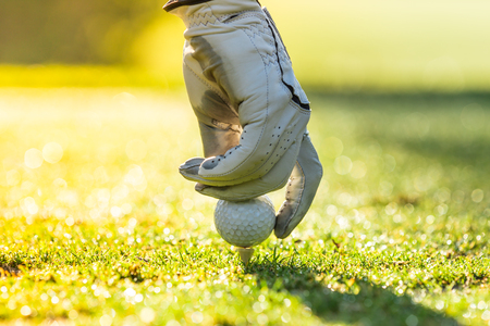 cut the competition: Close-up of golf ball during sunrise. Stock Photo