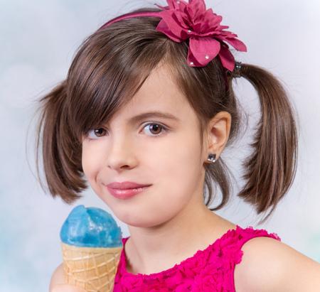 niña comiendo: niña con helado en el estudio, aislado en blanco. Foto de archivo
