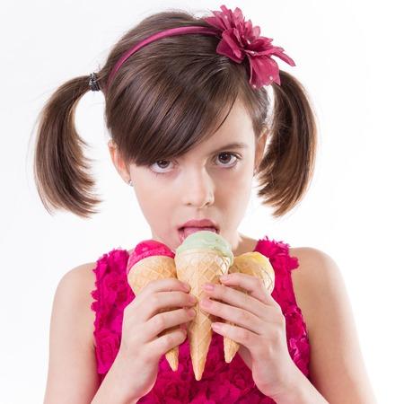 florecitas: niña con helado en el estudio, aislado en blanco. Foto de archivo