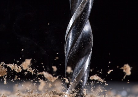 a drill: Drilling wooden plank, close-up.