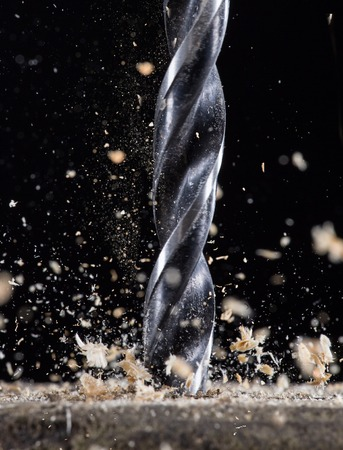 swarf: Drilling wooden plank, close-up.