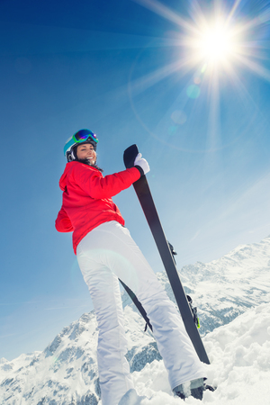 respite: Young woman with ski on mountains during sunny day.