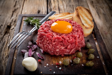 tartar: Close up of beef tartar with capers and small toasts. Stock Photo
