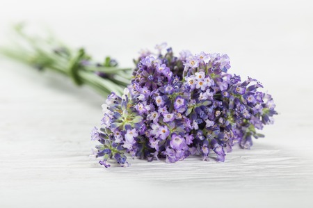 perfumed candle: Wellness treatments with lavender flowers on wooden table. Spa still-life.