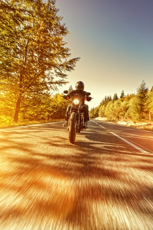 Man seat on the motorcycle on the forest road during sunrise. 免版税图像