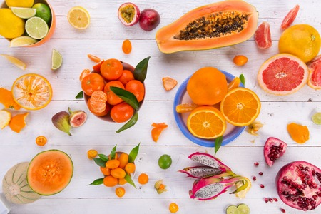 fruit background: Citrus fresh fruits on a wooden table, close-up.